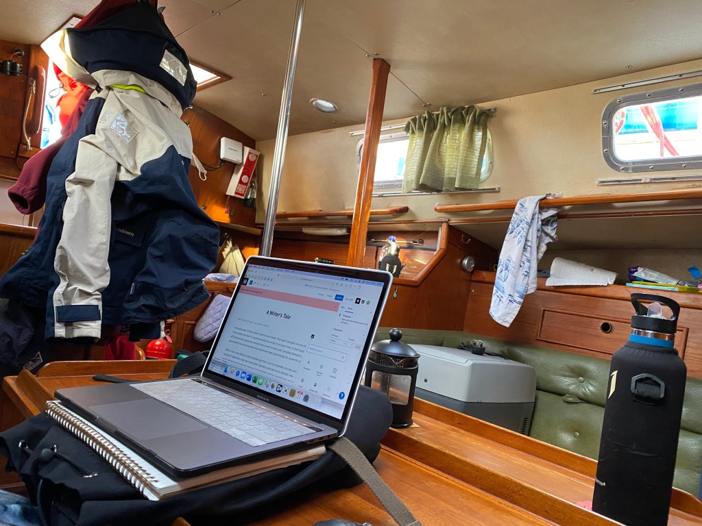 Image shows a photo of a laptop balanced on a rucksack inside the cabin of a boat.